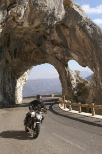 A motorbike with a rider driving on a mountain road just passed an arch made of rock.