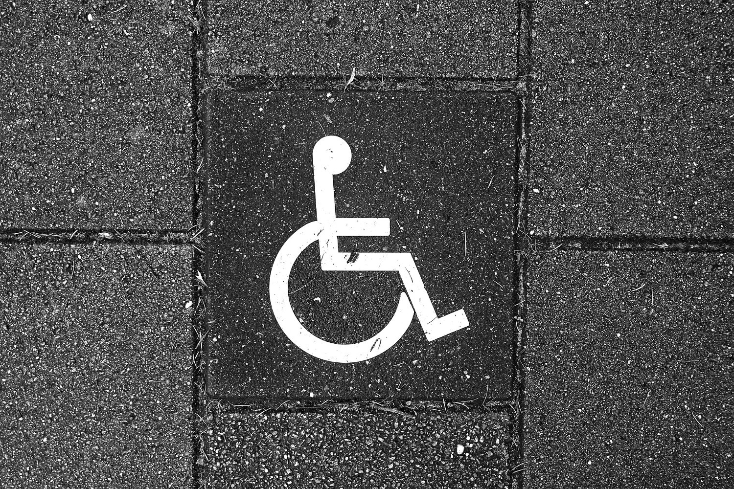 The pictograph of a person in a wheelchair on the pavement of a packing lot.
